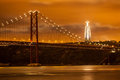 The de abril bridge over tagus river and big christ monument in lisbon at night portugal Stock Image