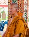 De boeddhistische monnik stelt voor een foto bij boeddhistische tempel van het drijven van damnoen saduak markt Stock Foto's