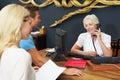 De controle van helping couple to van de hotelreceptionnist binnen Stock Afbeeldingen
