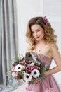 De foto van de manierstudio van mooi jong meisje met lang krullend haar in een roze kleding en bloemen Stock Afbeelding