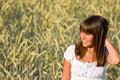 De jonge vrouw op graangebied geniet van zonsondergang Royalty-vrije Stock Foto's