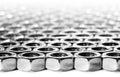 De noten die van de schroef op een witte oppervlakte leggen Stock Afbeelding