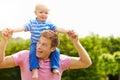 De rit van vadergiving young son op zijn schouders in tuin Royalty-vrije Stock Fotografie