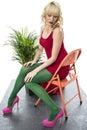 De sexy jonge stoel kort mini dress high pink heels van de vrouwenzitting Stock Afbeelding