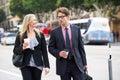 De straat van zakenmanand businesswoman in met meeneemkoffie Stock Afbeelding