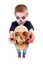 Dead head photo of eerie boy with human skull showing it to camera Stock Photo