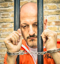 Dead man walking sad prisoner with handcuffs behind bars portrait of a waiting for death penalty Stock Images