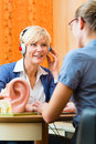 Deaf woman takes a hearing test older women or female pensioner with problem make and may need aid in the foreground is model Royalty Free Stock Photo