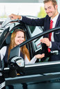 Dealer female client and auto in car dealership seller or salesman or customer presenting the interior decoration of new used cars Stock Photo