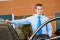 Dealer stands near a new car in the showroom dealerships Royalty Free Stock Photo