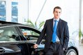 Dealer stands near a new car in the showroom put one hand on Royalty Free Stock Image