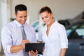 Dealership principal saleswoman handsome vehicle and looking at clipboard Royalty Free Stock Photos