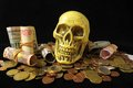 Death and money concept skull with currency over a black background Stock Photos
