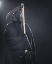 Death with scythe standing in fog the at night Royalty Free Stock Image
