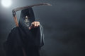 Death with scythe standing in the fog at night and points to you Stock Photography