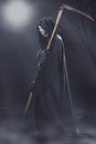 Death with scythe standing at night in the fog in the cemetery Royalty Free Stock Photography