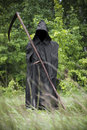 Death standing with scythe on hand in black coat a field Stock Image