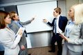 Debates two confident businessmen pointing at whiteboard while making speech at meeting Royalty Free Stock Photography