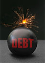 Debt bomb exploding labeled with burning fuse Royalty Free Stock Photography