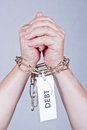 Debt chained hands with label attached concept Royalty Free Stock Images