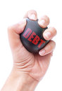 Debt reduction hand squeezing a stress ball labeled with Stock Images