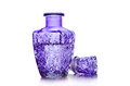 Decanter with water of purple glass filled closeup on a white background Stock Images