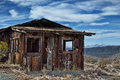 Decayed cabin on hill in randsberg california with beautiful cloudy sky and mountains in the back ground Royalty Free Stock Images