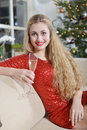 December girl new year smiling on a couch beside the christmas tree holding glass of champagne Stock Image