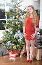 December girl red dressed standing beside the christmas tree Stock Photography