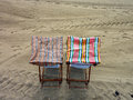 Deck chair two covered deckchairs on a sandy beach Royalty Free Stock Images