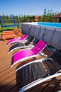 Deck chairs at backyard swimming pool several next to a garden Stock Photos
