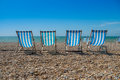 Deck chairs on a pebble beach blue Stock Photography