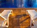 Deck chairs pool a pair of in front of a at a resort hotel Royalty Free Stock Images