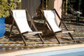 Deck chairs by swimming pool Royalty Free Stock Photography