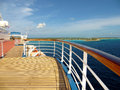 Deck and rail on a cruise ship photo of with the ocean an island in the background Royalty Free Stock Image