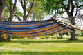 Deck swing foldable under oak trees in home garden Royalty Free Stock Image