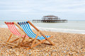Deckchairs on brighton beach brighton england two deckhairs with west pier behind east sussex Stock Photography