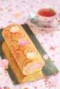 Deco roll cake with strawberry cream filling a cup of fruit tea on a light pink floral background Royalty Free Stock Photos