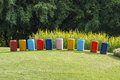 Decorate multi color concrete pipe stand on green grass. Royalty Free Stock Photo