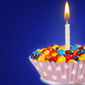 Decorated Birthday cupcake with one lit candle and colorful cand Royalty Free Stock Photo