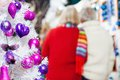 Decorated christmas tree and couple in store closeup of with senior background at Royalty Free Stock Image