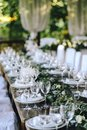 Decorated elegant wooden wedding table in rustic style with eucalyptus and flowers, porcelain plates and glasses Royalty Free Stock Photo