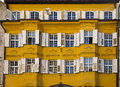 Decorated facade and windows bolzano italy yellow white shutters Royalty Free Stock Photos