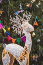 Decorated and illuminated toy reindeer under the Christmas tree Royalty Free Stock Photo
