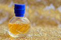 Decorated perfume bottle small over abstract golden background Royalty Free Stock Images