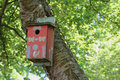 Decorated red birdhouse with painted decorations hangs from tree trunk with green foliage in the background Stock Photo
