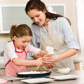 Decorating cake mother and daughter Royalty Free Stock Images