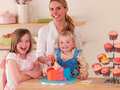 Decorating cakes happy young woman and children Stock Image