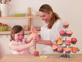 Decorating cakes happy young woman and girl Royalty Free Stock Photo