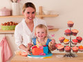 Decorating cakes happy young woman and toddler Stock Images
